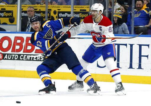 St. Louis Blues' Alex Pietrangelo (27) passes the puck as Montreal Canadiens' Max Pacioretty (67) watches during the third period of an NHL hockey game Tuesday, Jan. 30, 2018, in St. Louis. The Blues won 3-1.