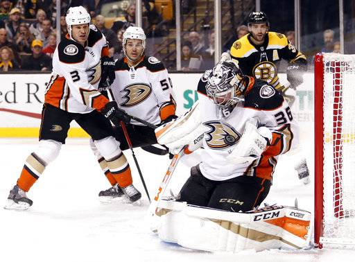 Anaheim Ducks goaltender John Gibson makes a save as Kevin Bieksa (3) and Antoine Vermette and Boston Bruins' Patrice Bergeron watch during the second period of an NHL hockey game in Boston on Tuesday, Jan. 30, 2018.