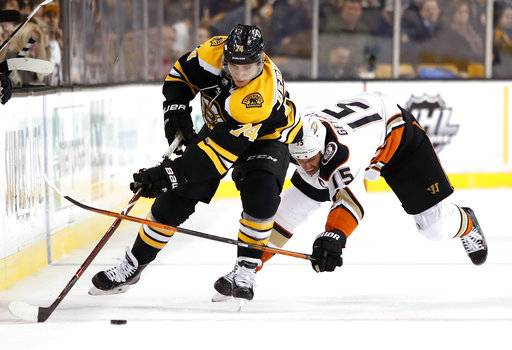 Anaheim Ducks' Ryan Getzlaf (15) tries to stop Boston Bruins' Jake DeBrusk during the second period of an NHL hockey game Tuesday, Jan. 30, 2018, in Boston.
