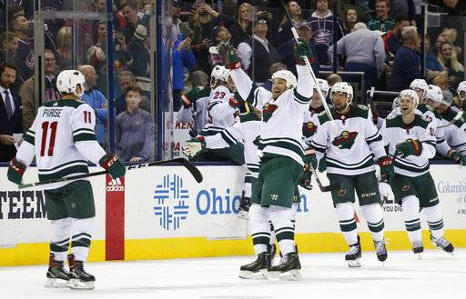 Minnesota Wild players celebrate their win over the Columbus Blue Jackets in an NHL hockey game Tuesday, Jan. 30, 2018, in Columbus, Ohio. The Wild beat the Blue Jackets 3-2 in a shootout.