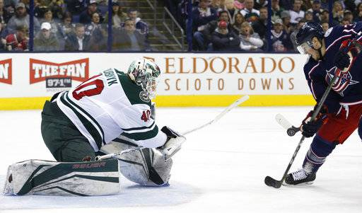 Minnesota Wild's Devan Dubnyk, left, makes a save against Columbus Blue Jackets' Cam Atkinson during the second period of an NHL hockey game Tuesday, Jan. 30, 2018, in Columbus, Ohio.