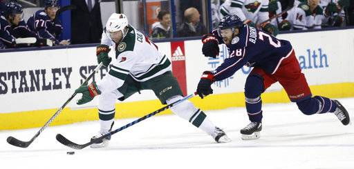 Minnesota Wild's Matt Cullen, left, carries the puck up ice as Columbus Blue Jackets' Oliver Bjorkstrand, of Denmark, defends during the first period of an NHL hockey game Tuesday, Jan. 30, 2018, in Columbus, Ohio.