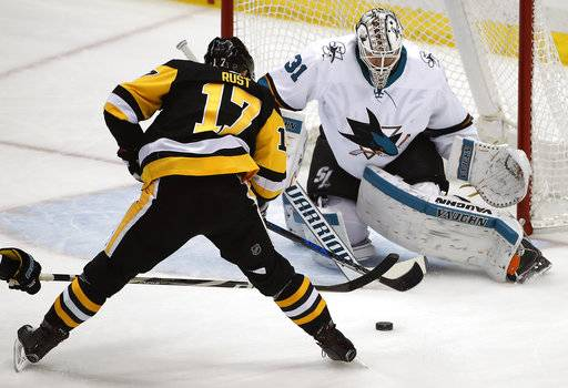 Pittsburgh Penguins' Bryan Rust (17) puts a shot between the pads of San Jose Sharks goaltender Martin Jones (31) for a goal during the first period of an NHL hockey game in Pittsburgh, Tuesday, Jan. 30, 2018.