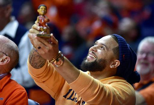 Former Illinois player Deron Williams holds up a bobblehead figure of himself during a timeout in the first half of an NCAA college basketball game between Illinois and Rutgers in Champaign, Ill., Tuesday, Jan. 30, 2018.