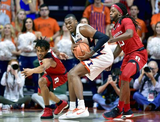 Illinois forward Leron Black (12) protects the ball from the reach of Rutgers guard Corey Sanders, left, and forward Deshawn Freeman (33) during the first half of an NCAA college basketball game in Champaign, Ill., Tuesday, Jan. 30, 2018.