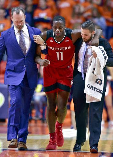 Trainers help Rutgers forward Eugene Omoruyi (11) off the court during the first half of the team's NCAA college basketball game against Illinois in Champaign, Ill., Tuesday, Jan. 30, 2018.