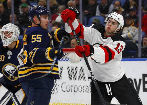Buffalo Sabres defenseman Rasmus Ristolainen (55) and New Jersey Devils forward Nico Hischier (13) get the sticks up during the second period of an NHL hockey game, Tuesday, Jan. 30, 2018, in Buffalo, N.Y.