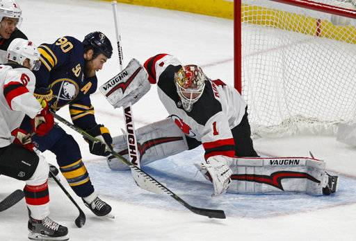 A shot by Buffalo Sabres forward Ryan O'Reilly (90) is stopped by New Jersey Devils goalie Keith Kinkaid (1) during the third period of an NHL hockey game, Tuesday, Jan. 30, 2018, in Buffalo, N.Y.