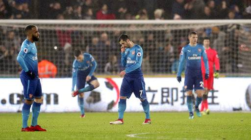 Arsenal's Henrikh Mkhitaryan, center, looks dejected after Arsenal concede their third goal of the game during the English Premier League soccer match between Swansea City and Arsenal at the Liberty Stadium, Swansea, Wales, Tuesday, Jan. 30, 2018. (Nick Potts/PA via AP)