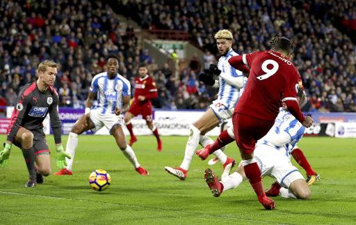 Liverpool's Roberto Firmino, right, scores his side's second goal of the game against Huddersfield Town during their English Premier League soccer match at the John Smith's Stadium in Huddersfield, England, Tuesday Jan. 30, 2018. (Martin Rickett/PA via AP)
