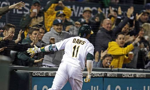 FILE - In this April 4, 2017, file photo, Oakland Athletics' Rajai Davis celebrates with fans as he scores on a throwing error after hitting a two-run triple off Los Angeles Angels' Bud Norris during the seventh inning of a baseball game in Oakland, Calif. The Athletics will expand protective netting between the stands and the playing field to the far ends of both dugouts ahead of the 2018 season.