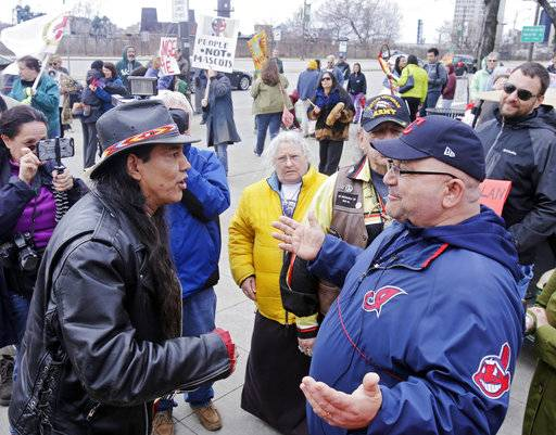FILE - In this April 10, 2015, file photo, Philip Yenyo, left, executive director of the American Indians Movement for Ohio, talks with a Cleveland Indians fan before a baseball game against the Detroit Tigers in Cleveland. The Indians are dropping the Chief Wahoo logo, front lower right, from their uniforms next year after decades of protests and complaints that the grinning, red-faced caricature used in one version or another since 1947 is racist.
