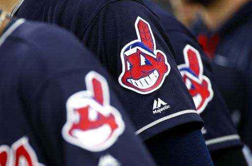 FILE - In this June 19, 2017 file photo, members of the Cleveland Indians wear uniforms featuring mascot Chief Wahoo as they stand on the field for the national anthem before a baseball game against the Baltimore Orioles in Baltimore. The Cleveland Indians are taking the divisive Chief Wahoo logo off their jerseys and caps, starting in 2019.