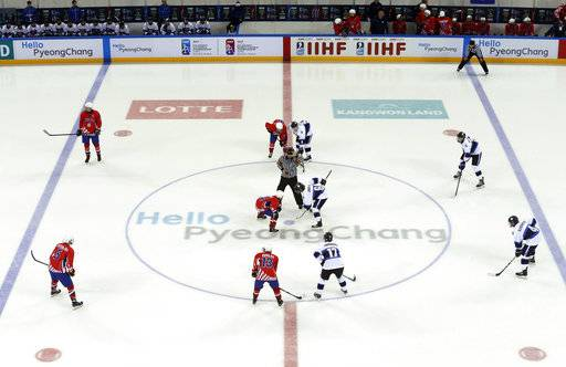 FILE - In this April 4, 2017, file photo, players of Croatia, left in red, and Estonia take positions for the opening faceoff in an under-18 World Championship Division II Group A hockey game at Kwandong Hockey Center in Gangneung, South Korea. Olympic hockey played on wider international-sized ice changes everything about the style of play and is much different than the NHL. The United States and Canada in the past have needed to adjust to the bigger rinks, though most players going to South Korea are currently playing on it.