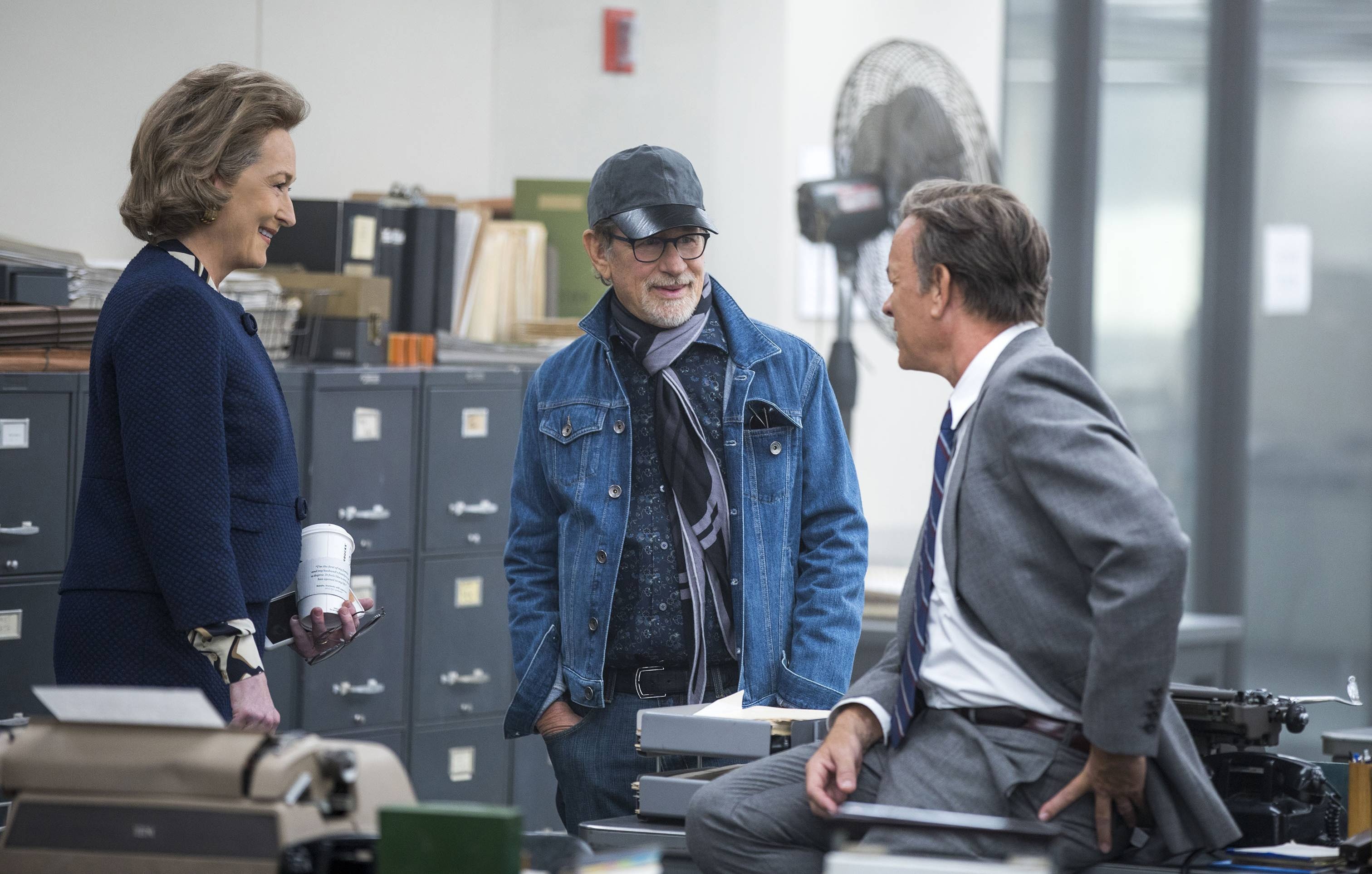 "Director Steven Spielberg chats with stars Meryl Streep and Tom Hanks on the set of ""The Post."""