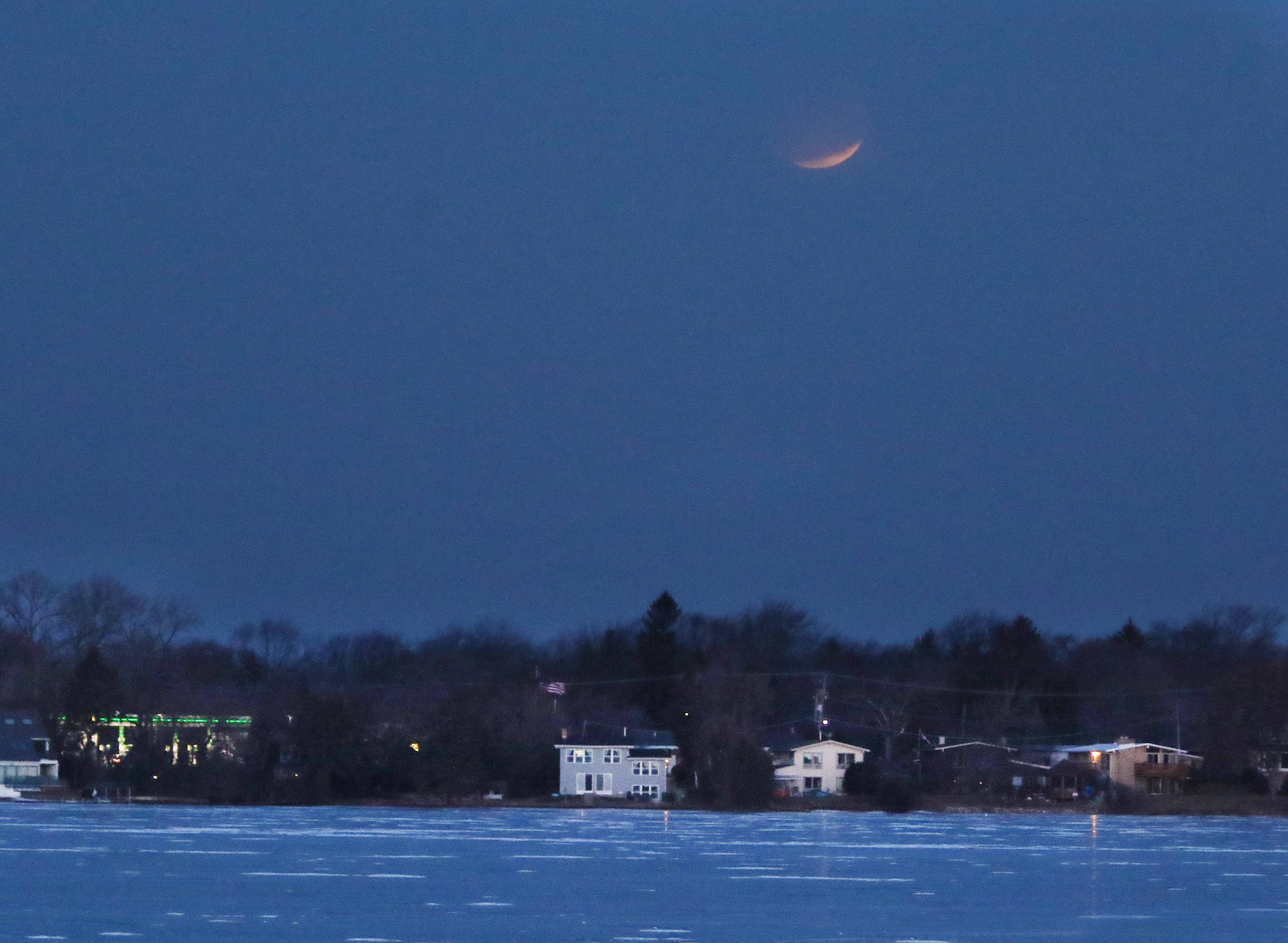 Gilbert R. Boucher II/gboucher@dailyherald.comThe super blue moon sets over Lake Zurich Wednesday morning. The moon came out from behind the clouds to clear skies for the lunar eclipse before falling behind clouds as it neared the horizon.