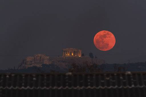 A super blue blood moon rises behind the 2,500-year-old Parthenon temple on the Acropolis of Athens, Greece, on Wednesday, Jan. 31, 2018. On Wednesday, much of the world will get to see not only a blue moon which is a supermoon, but also a lunar eclipse, all rolled into one celestial phenomenon.