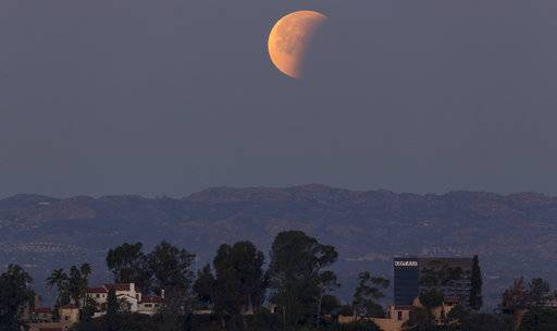A super blue blood moon is seen setting behind the Hollywood hills in Los Angeles on Wednesday Jan. 31, 2018. The moon is putting on a rare cosmic show. It's the first time in 35 years a blue moon has synced up with a supermoon and a total lunar eclipse. NASA is calling it a lunar trifecta: the first super blue blood moon since 1982. That combination won't happen again until 2037.