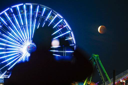 A man is silhouetted takes photo of a rare occurrence called a 'Super Blue Blood Moon' at Santa Monica Beach in Santa Monica, Calif., Wednesday, Jan. 31, 2018. It's the first time in 35 years a blue moon has synced up with a supermoon and a total lunar eclipse. Hawaii and Alaska have the best seats, along with the Canadian Yukon, Australia and Asia.