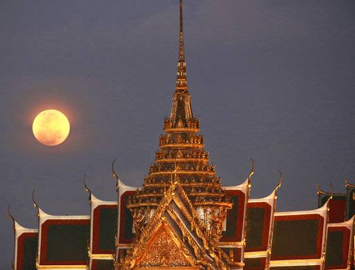 A full moon rises beside the Grand Palace in Bangkok, Thailand , Wednesday, Jan. 31, 2018. The moon is putting on a rare cosmic show. It's the first time in 35 years a blue moon has synced up with a supermoon and a total lunar eclipse.