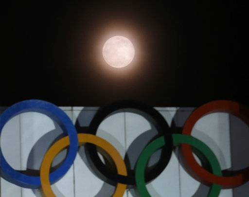 The full moon is seen over the Olympic rings on display at the Peace Gate at the Olympic Park in Seoul, South Korea, Wednesday, Jan. 31, 2018. The moon is putting on a rare cosmic show. It's the first time in 35 years a blue moon has synced up with a supermoon and a total lunar eclipse.