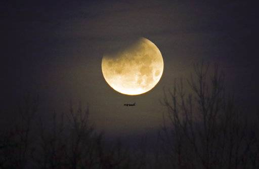 A plane passes by as the moon sets over trees during a phenomena that combined a supermoon, a blue moon and a lunar eclipse in Charlotte, N.C., Wednesday, Jan. 31, 2018. Only a partial eclipse was visible on the East Coast.