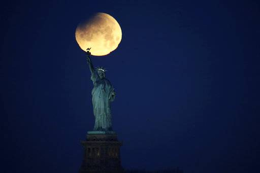 The Statue of Liberty is backdropped by a supermoon, Wednesday, Jan. 31, 2018, seen from the Brooklyn borough of New York. The supermoon, which is the final of three consecutive supermoons, also experience lunar eclipse as it set over the horizon, but only a partial eclipse was visible in the East Coast.