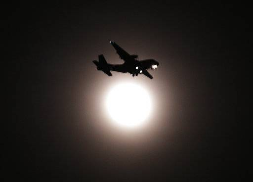 An airplane passes the full moon on its final approach before landing in Seoul, South Korea, Wednesday, Jan. 31, 2018. The moon is putting on a rare cosmic show. It's the first time in 35 years a blue moon has synced up with a supermoon and a total lunar eclipse.