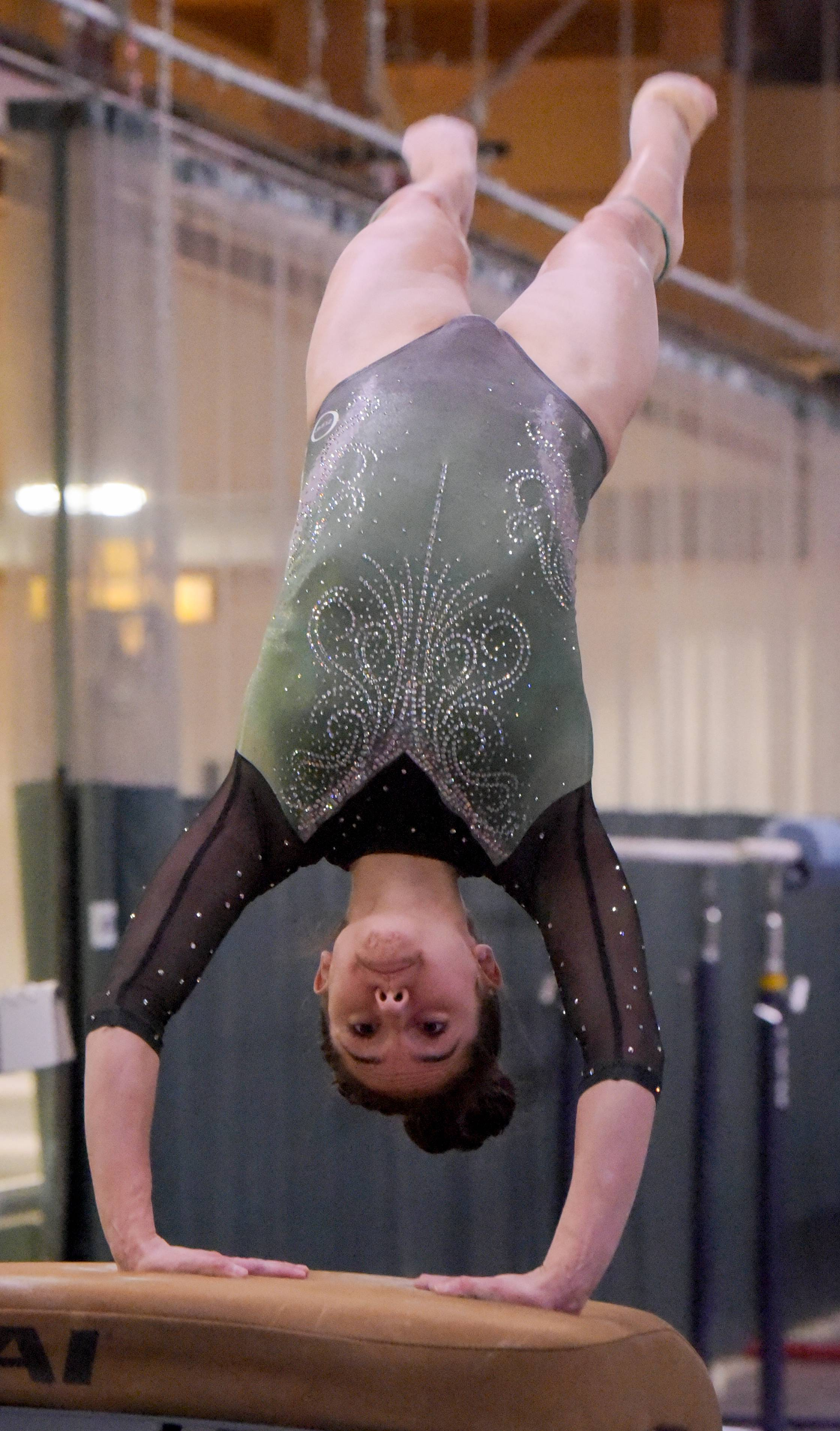 Glenbard West's Taylor Ramirez competes on the vault during the Glenbard West regional gymnastics meet on Wednesday, Jan. 31, 2018.