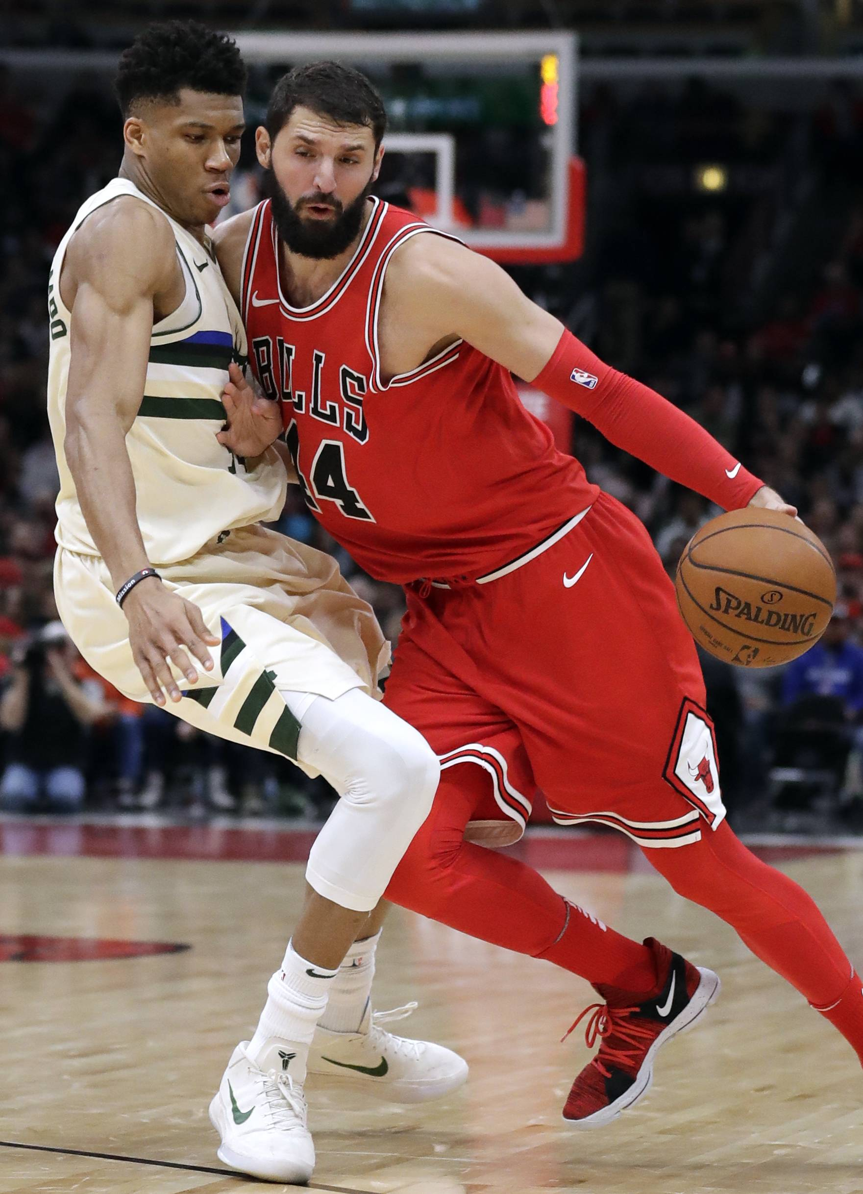 Chicago Bulls forward Nikola Mirotic, right, drives against Milwaukee Bucks forward Giannis Antetokounmpo during the second half of an NBA basketball game Sunday, Jan. 28, 2018, in Chicago.