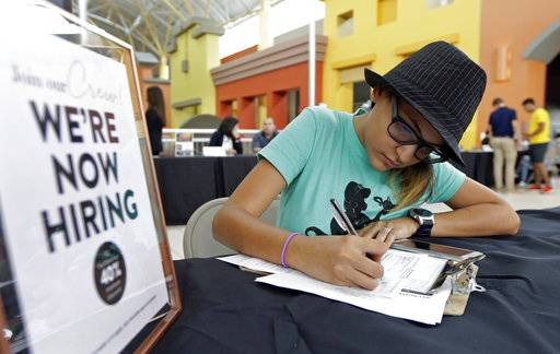 FILE - In this Oct. 4, 2017 file photo, job seeker Alejandra Bastidas fills out an application at a job fair in Sweetwater, Fla.  U.S. workers' wages and benefits grew 2.6 percent last year, the fastest 12-month pace since the spring of 2015. The 12-month gain in wages and benefits came despite a slight slowdown at the end of last year with wages and benefits rising 0.6 percent in the fourth quarter, a tiny dip from a 0.7 percent gain in the third quarter. Still, the 12-month gain was an improvement from a 2.2 percent gain for the 12 months ending in December 2016.