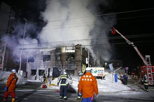 Firefighters work at the scene of a fire in Sapporo, northern Japan, early Thursday, Feb. 1, 2018.  Japanese media say 11 people have died in a fire that engulfed a home for elderly welfare recipients in northern Japan. The fire broke out before midnight Thursday in Sapporo, the main city on the island of Hokkaido. (Yuya Shino/Kyodo News via AP)