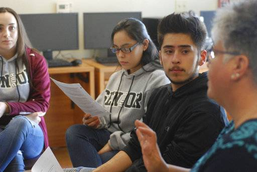 In this Jan. 18, 2018, photo, high school seniors John King, second from right, Ashley Zapata, second from left, and Felicity Sealy, left, listen as English and college-preparation teacher Rhonda Gardner leads a discussion about how to adjust to the academic, financial and social pressures of collegiate life on Thursday, Jan. 18, 2018, in Santa Fe, N.M.