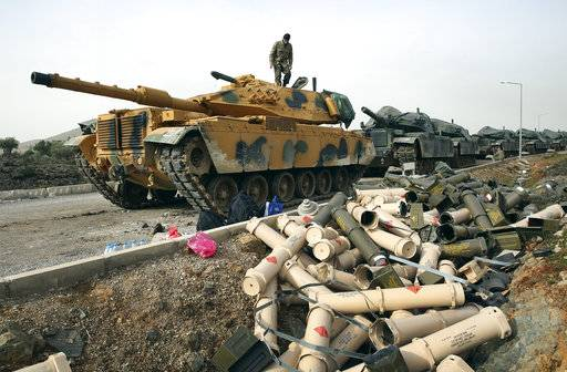 FILE -- In this Monday January 22, 2018 file photo, Turkish Army soldiers prepare their tanks next to empty shells at a staging area on the outskirts of the village of Sugedigi, Turkey, on the border with Syria. Syria's Kurdish militia is growing frustrated with its patron, the United States, and is pressing it to do more to stop Turkey's assault on Afrin. Their complaints reflect the differing agendas. The Kurds want to ensure their self-rule, while the U.S. wants them to focus on governing the territory they wrested from IS militants.
