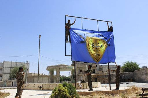 FILE - This file photo released Aug. 8, 2016 by Hawar news, the news agency for the semi-autonomous Kurdish areas in Syria (ANHA), shows the Kurdish-led Syria Democratic Forces raising their flag in the town of Manbij after driving Islamic State militants out of the area, in Aleppo province, Syria. The militia is growing frustrated with its patron, the United States, and is pressing it to do more to stop Turkey's assault on Afrin. Their complaints reflect the differing agendas. The Kurds want to ensure their self-rule, while the U.S. wants them to focus on governing the territory they wrested from IS militants. (ANHA via AP, File)