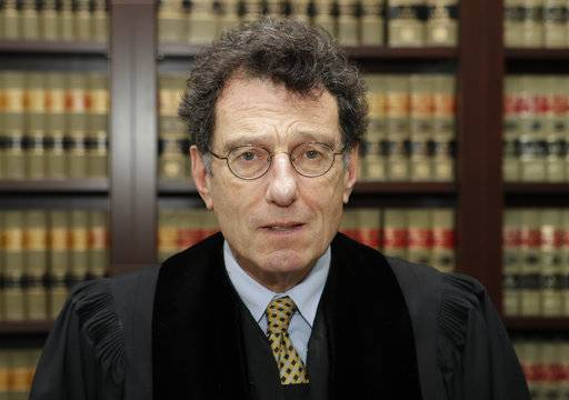 "FILE - This Jan. 11, 2018 file photo shows judge Dan Polster in his office in Cleveland. Polster has called the opioid addiction epidemic ""100 percent man-made� and asserted that other branches of government have ""punted� on solving it. Polster has made clear that he wants to use the cases before him as a way to forge a solution to the opioid crisis _ not just a legal resolution."