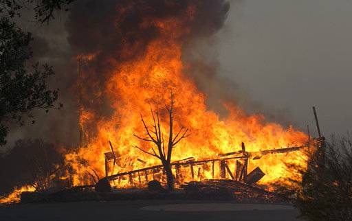 FILE - In this Monday Oct. 9, 2017 file photo flames from a wildfire consume a home, near Napa, Calif. Insurance claims for last year's deadly California wildfires have reached $11.8 billion, Insurance Commissioner Dave Jones said Wednesday, Jan. 31, 2018.