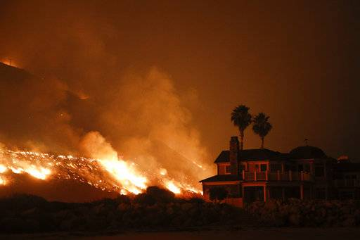 FILE -- In this Tuesday, Dec. 5, 2017 file photo a wildfire threatens homes as it burns along the 101 Freeway in Ventura, Calif. Insurance claims for last year's deadly California wildfires have reached $11.8 billion, Insurance Commissioner Dave Jones said Wednesday, Jan. 31, 2018.