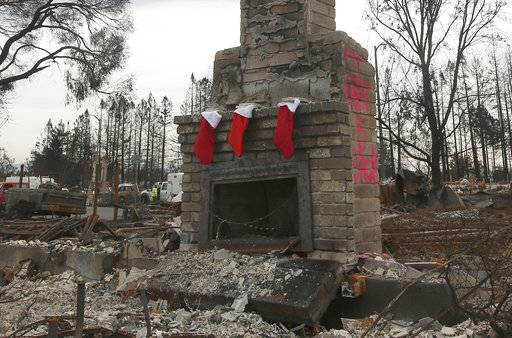 FILE -- In this Dec. 2, 2017 file photo Christmas stockings hang from a fireplace at a home destroyed in an October wildfire in the Coffey Park area of Santa Rosa, Calif. Insurance claims for last year's deadly California wildfires have reached $11.8 billion, Insurance Commissioner Dave Jones said Wednesday, Jan. 31, 2018.