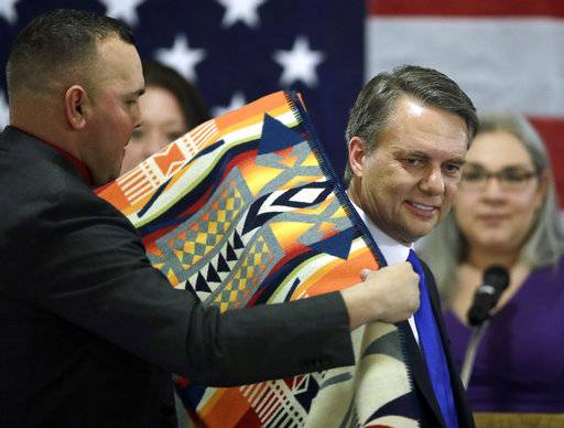 "Gov. Jeff Colyer receives a gift from the four tribes of the state after being sworn in as Governor of Kansas during a ceremony at the Statehouse in Topeka, Kan., Wednesday, Jan. 31, 2018. Colyer promised a ""new day"" of openness shortly after taking the oath Wednesday as Kansas' governor, addressing the public and a GOP-controlled Legislature that is deeply divided over a court order to increase state spending on public schools."