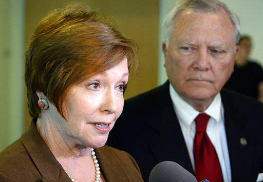 FILE - In this Oct. 16, 2014 file photo, Brenda Fitzgerald, Georgia Department of Public Health commissioner, left, and Georgia Gov. Nathan Deal respond to questions in Atlanta.  U.S. officials announced that Fitzgerald, the director of the nation's top public health agency has resigned because of financial conflicts of interest. On Tuesday, Jan. 30, 2018,  the U.S. Department of Health and Human Services officials said Fitzgerald's complex financial interests had caused conflicts of interest that made it difficult to do her job. Alex Azar, who was sworn in as head of the department Monday, accepted her resignation.