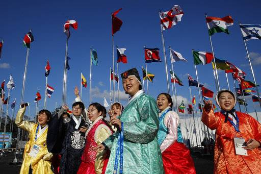 A group of volunteers wearing handbook, Korean traditional dress, greet athletes entering the Olympic Village as flags including North Korea's, fly prior to the 2018 Winter Olympics in Gangneung, South Korea, Thursday, Feb. 1, 2018.
