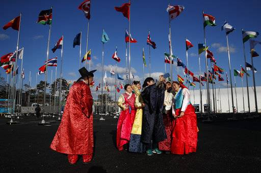 A group of volunteers wearing handbook, Korean traditional dress, take selfies at the Olympic Village prior to the 2018 Winter Olympics in Gangneung, South Korea, Thursday, Feb. 1, 2018.