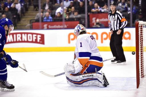 Toronto Maple Leafs defenseman Travis Dermott (23) scores past New York Islanders goaltender Thomas Greiss (1) for his first career goal, during the second period of an NHL hockey game Wednesday, Jan. 31, 2018, in Toronto. (Frank Gunn/The Canadian Press via AP)
