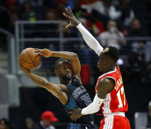 Charlotte Hornets guard Kemba Walker (15) looks for an open teammate as Atlanta Hawks guard Dennis Schroeder (17) defends during the first half of an NBA basketball game Wednesday, Jan. 31, 2018, in Atlanta.
