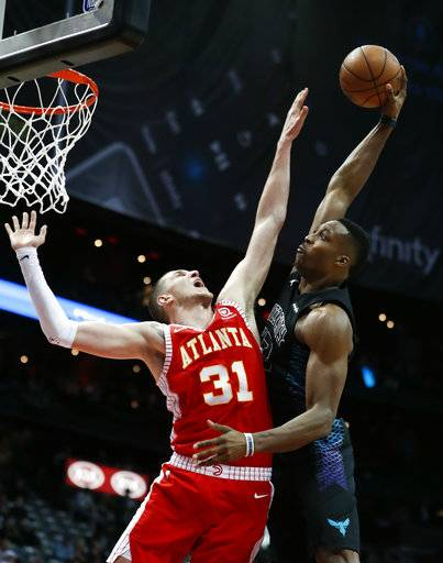 Charlotte Hornets center Dwight Howard. right, is fouled by Atlanta Hawks forward Mike Muscala (31) during the second half of an NBA basketball game Wednesday, Jan. 31, 2018, in Atlanta. Charlotte won 123-110.
