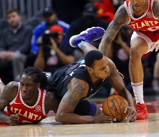 Charlotte Hornets guard Treveon Graham (21) and Atlanta Hawks forward Taurean Prince (12) dive for a loose ball during the first half of an NBA basketball game Wednesday, Jan. 31, 2018, in Atlanta.