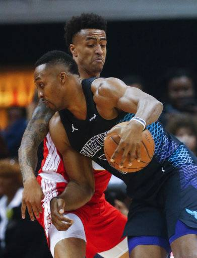Charlotte Hornets center Dwight Howard drives against Atlanta Hawks forward John Collins during the first half of an NBA basketball game Wednesday, Jan. 31, 2018, in Atlanta.