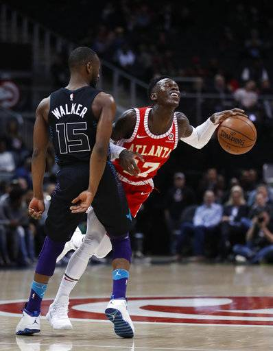 Atlanta Hawks guard Dennis Schroeder (17) crashes into Charlotte Hornets guard Kemba Walker (15) during the first half of an NBA basketball game Wednesday, Jan. 31, 2018, in Atlanta.