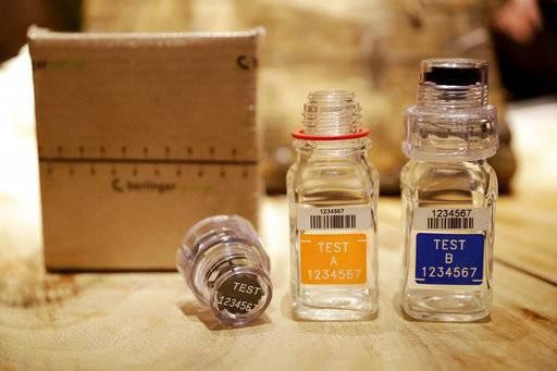 FILE - In this Dec. 12, 2016, file photo, the A and B sample bottles from the latest Berlinger Special BEREG-Kit for human urine doping testing stand posed for photographs in London. The World Anti-Doping Agency (WADA) recommended to the International Olympic Committee that it use 2016 doping sample bottles for the upcoming Winter Olympics after the agency's inquiry into the 2017 version showed the bottles could be re-opened after a sample was produced.